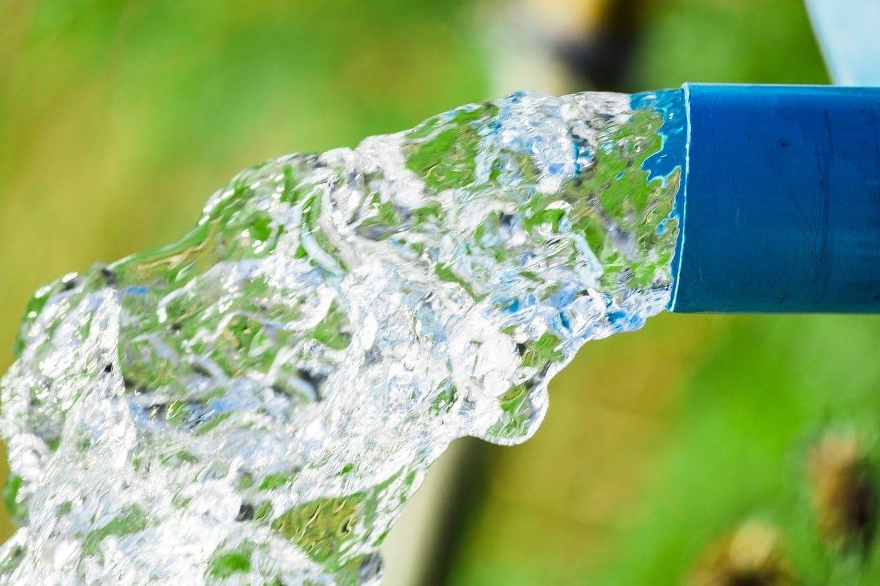 Tubería azul de agricultura por el que sale agua corriente