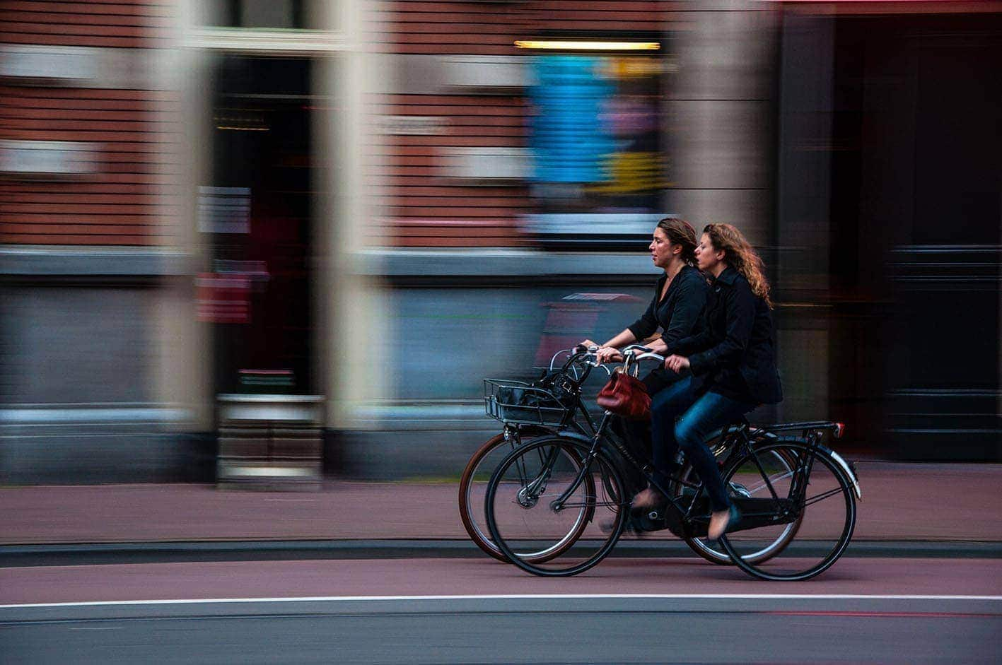 Image of two women riding a bicycle