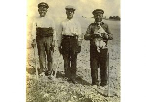 Three roadmen in Villamanrique, one of them holding a dog, Ciudad Real, in 1930.