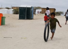 A boy runs behind a tire on a dirt esplanade