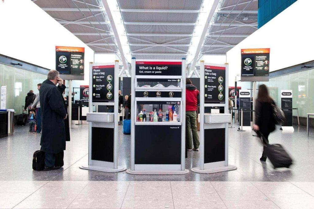 Imagen de un stand en el aeropuerto en el que se ven botellas de plástico, líquidos, etc