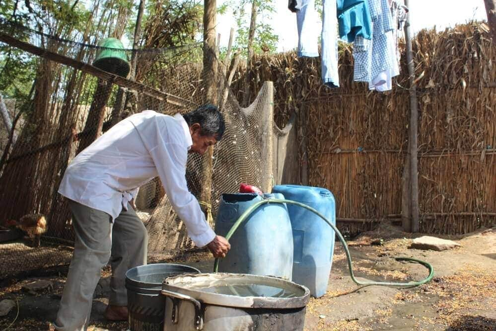 Image of a man using the hose that supplies running water