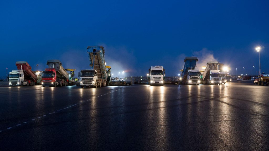 Image of the renovated area of the T4 at the airport of barajas, several trucks circulate at night on the track