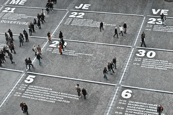 people walking between days and hours marked on the floor like a calendar