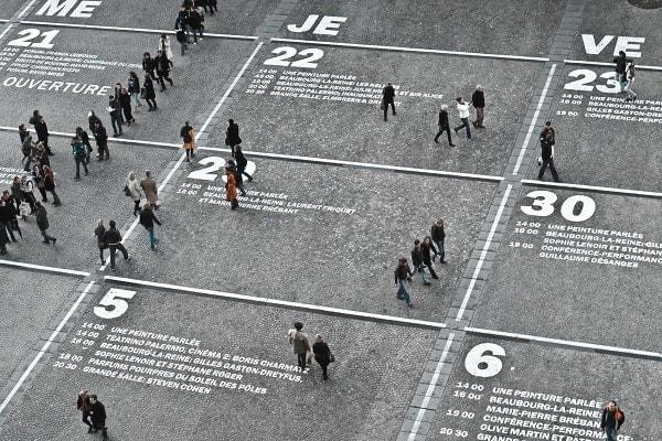 personas caminando entre los dias y horas marcados en el suelo como un calendario