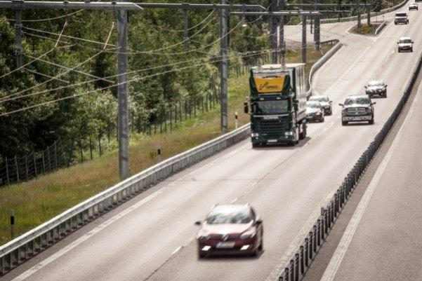Foto de una carretera electrificada con varios coches y un camión.