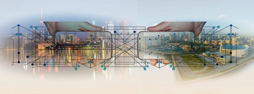 Two smartphones found simulate exchanging large amounts of data. A city in the background and two hands that support them