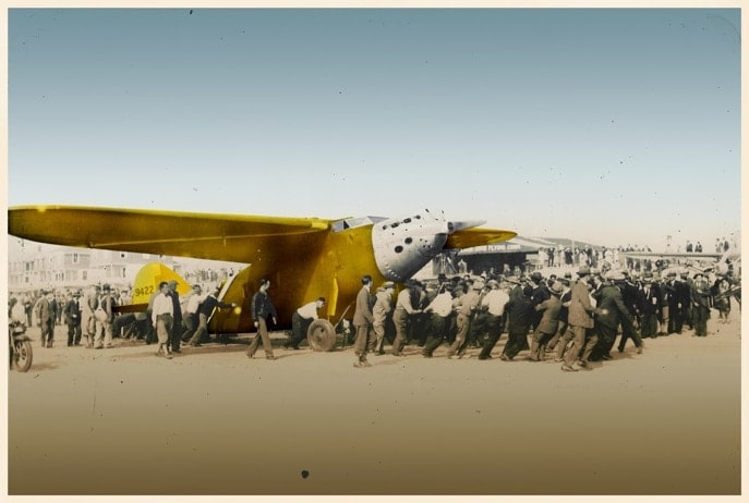 Image of the landing of the Yellow Bird plane on the beach of Oyambre and many people surround the aircraft
