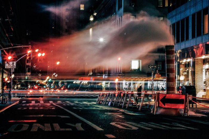 Foto nocturna de Nueva York donde se puede ver una obra, humo y semaforos en rojo