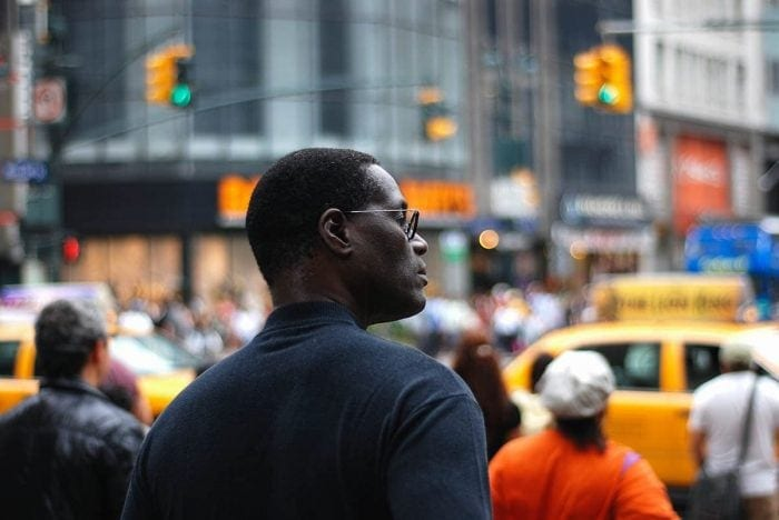 image of a man in profile on a street with yellow taxis and semaphores