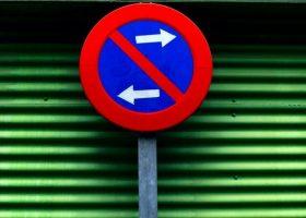 Foto de prohibido aparcar a ambos lados de la señal delante de cierre metalico verde