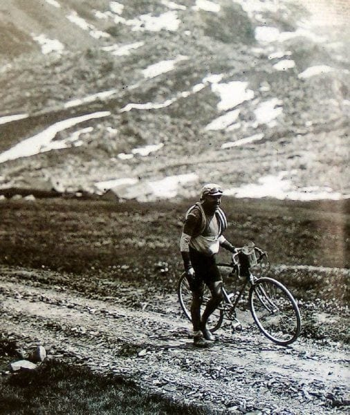 Old image of a cyclist holding the bicycle