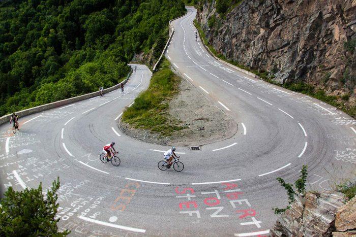 Imagen de una curva en carretera de montaña y 7 ciclistas subiendo