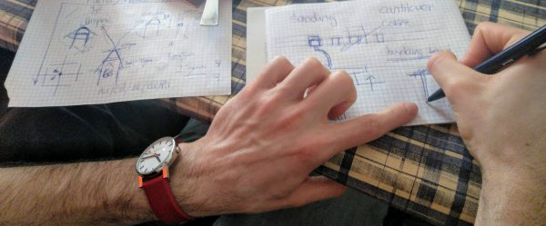 Aprende a pronunciar Photo of the hands of a person who is drawing outlines on some sheets