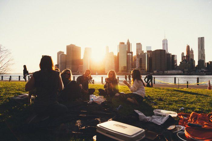 Foto de un grupo de personas sentadas en el cesped de un parque con una ciudad de fondo