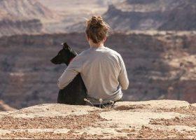 Chica con mascota de espaldas mirando desde un acantilado
