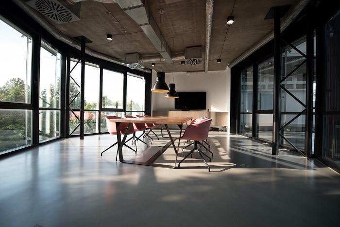 Espacio diáfano con mesa de reuniones y ventanas grandes